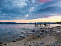 在日落的沙子多岩石的海滩 库存照片