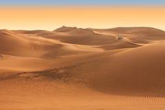 在日落的沙漠徒步旅行队在迪拜附近。 阿拉伯联合酋长国 库存图片