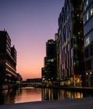 在日落的河沿现代大厦 免版税库存照片