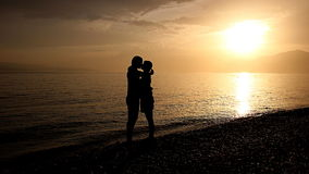 在日落的浪漫亲吻由海 免版税库存图片