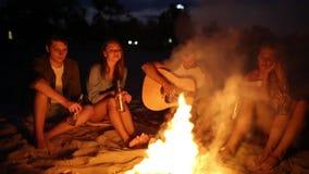 在日落的海滩党与篝火 和唱歌对吉他的朋友坐在篝火附近,饮用的啤酒 人和 股票视频