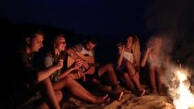 在日落的海滩党与篝火 和唱歌对吉他的朋友坐在篝火附近,饮用的啤酒 年轻 股票录像