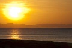 在日落的海滩金黄展望期山 免版税库存图片