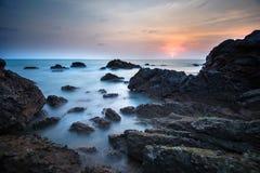 在日落的海运和岩石 免版税库存图片