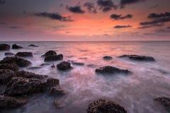 在日落的海运和岩石 库存照片