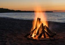 在日落的海滩篝火 库存图片
