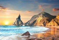 在日落的海洋风景,大岩石和石头靠岸 库存图片
