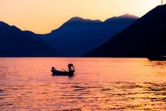 在日落的渔夫剪影在科托尔海湾黑山的山背景 免版税库存照片