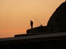 在日落的渔夫剪影 库存图片