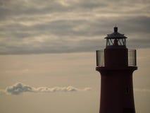 在日落的灯塔剪影 库存图片