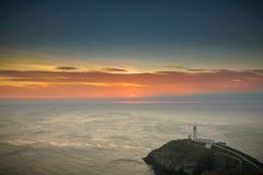在日落的灯塔,南堆, Anglesey,北部威尔士 库存图片