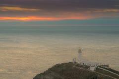 在日落的灯塔,南堆, Anglesey,北部威尔士 免版税图库摄影