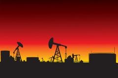 在日落的炼油厂和油泵剪影 库存照片