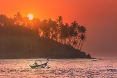 在日落的热带海滩与渔夫和海 免版税图库摄影