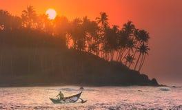 在日落的热带海滩与渔夫和海 库存照片