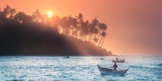 在日落的热带海滩与渔夫和海 免版税库存照片