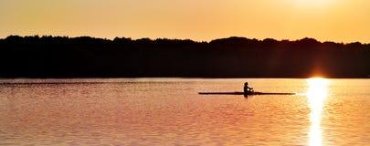 在日落的独木舟在湖 免版税库存图片