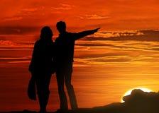 在日落的现出轮廓的夫妇 免版税库存照片