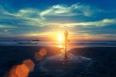 在日落的瑜伽剪影在海岸 免版税库存照片