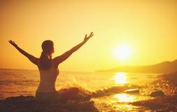 在日落的瑜伽在海滩 执行女子瑜伽 免版税图库摄影