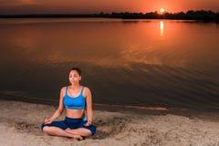 在日落的瑜伽在海滩 免版税图库摄影