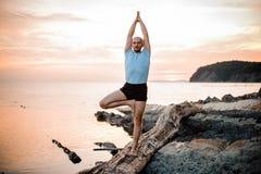 在日落的瑜伽姿势由人 免版税库存图片
