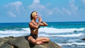 在日落的瑜伽实践 雍妇女在莲花姿势在慢的美丽的早晨海滩坐石头并且思考 股票录像