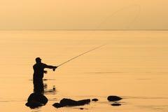 在日落的用假蝇钓鱼 免版税库存照片