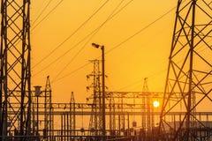 在日落的电力设备中现出轮廓高压电柱子定向塔 免版税库存照片