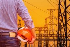 在日落的电力设备分站设计拿着与高压电定向塔柱子的黄色安全帽 库存照片