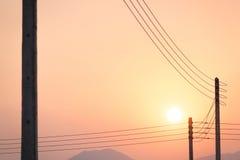 在日落的电子和导线 图库摄影