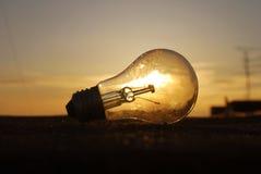 在日落的电灯泡在云彩背景 免版税库存照片