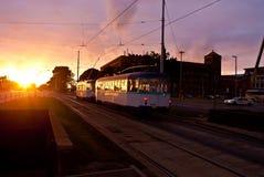 在日落的电车在城市街道 库存图片
