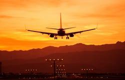 在日落的着陆飞机 免版税图库摄影