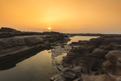 在日落的石反射的水 免版税库存图片