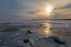在日落的石头、冰川和冻结的海在阳光下` s光芒 33c 1月横向俄国温度ural冬天 图库摄影