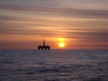 在日落的石油平台 库存图片