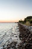 在日落的石防波堤 库存图片