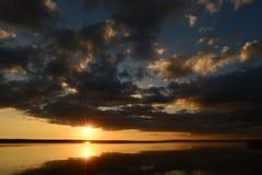 在日落的秋天多云天空根据阳光明亮的闪光  免版税库存图片