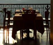 在日落的空的室外餐馆桌 免版税库存图片