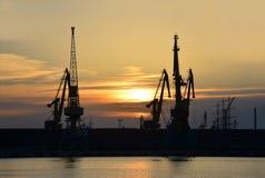 在日落的端口货物起重机 免版税图库摄影
