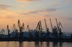 在日落的端口货物起重机 库存照片