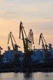 在日落的端口货物起重机 免版税库存图片