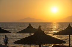 在日落的竹沙滩伞 免版税库存照片