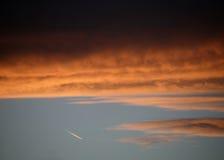 在日落的红色和橙色云彩与喷气机蒸气落后 免版税库存照片