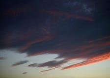 在日落的红色橙色和蓝色云彩 免版税库存图片