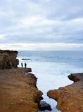 在日落的红色花岗岩海岸线,钓鱼在日落的无法认出的人 免版税库存照片