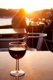 在日落的红葡萄酒玻璃 免版税库存图片