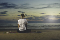 年轻在日落的纹身花刺人实践的瑜伽 库存图片
