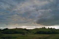 在日落的美丽的积云在领域和多小山谷 库存照片